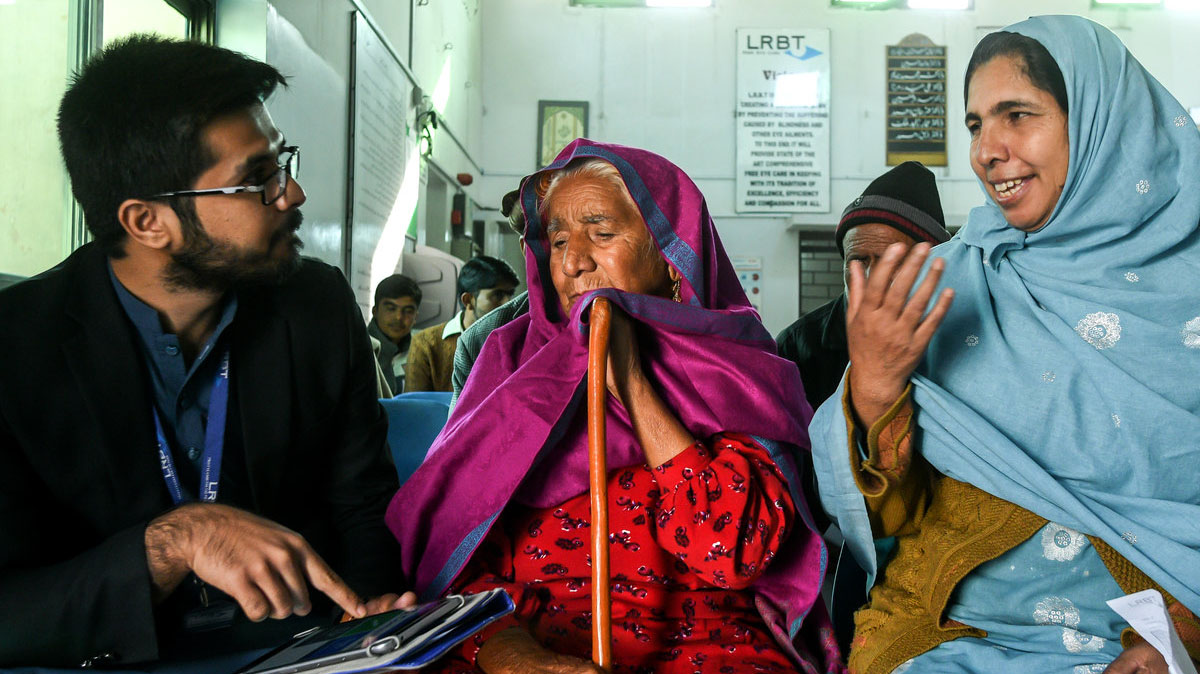 An elderly woman and a younger woman sit next to a man who holds a clipboard, in a hospital waiting area.