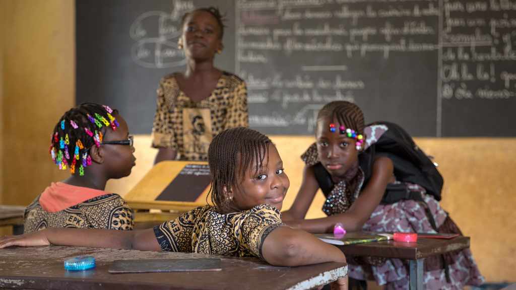 A smiling girl in a classroom.