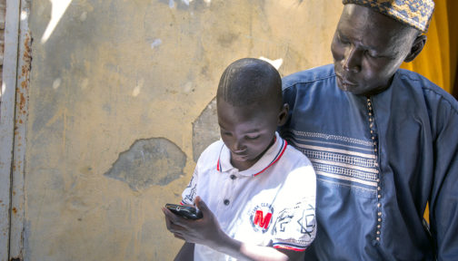 A boy using a phone with his father sitting behind.