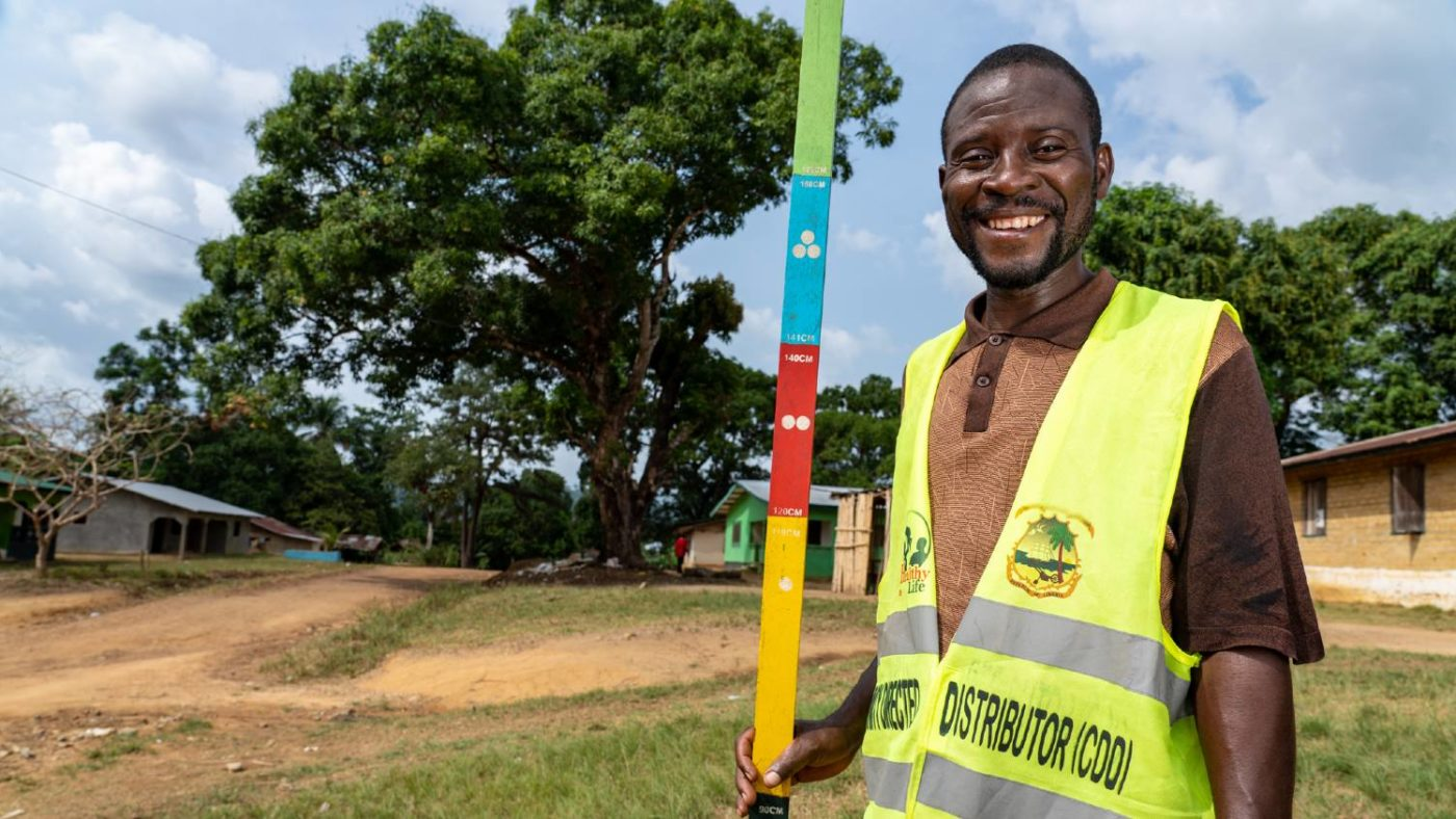 A man stands for a portrait while holding a colourful dose pole.