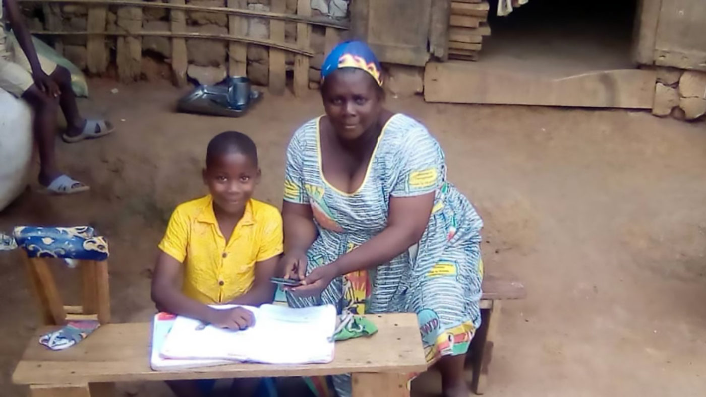 A boy sits outside his house with his mother who is helping him fill in school work.
