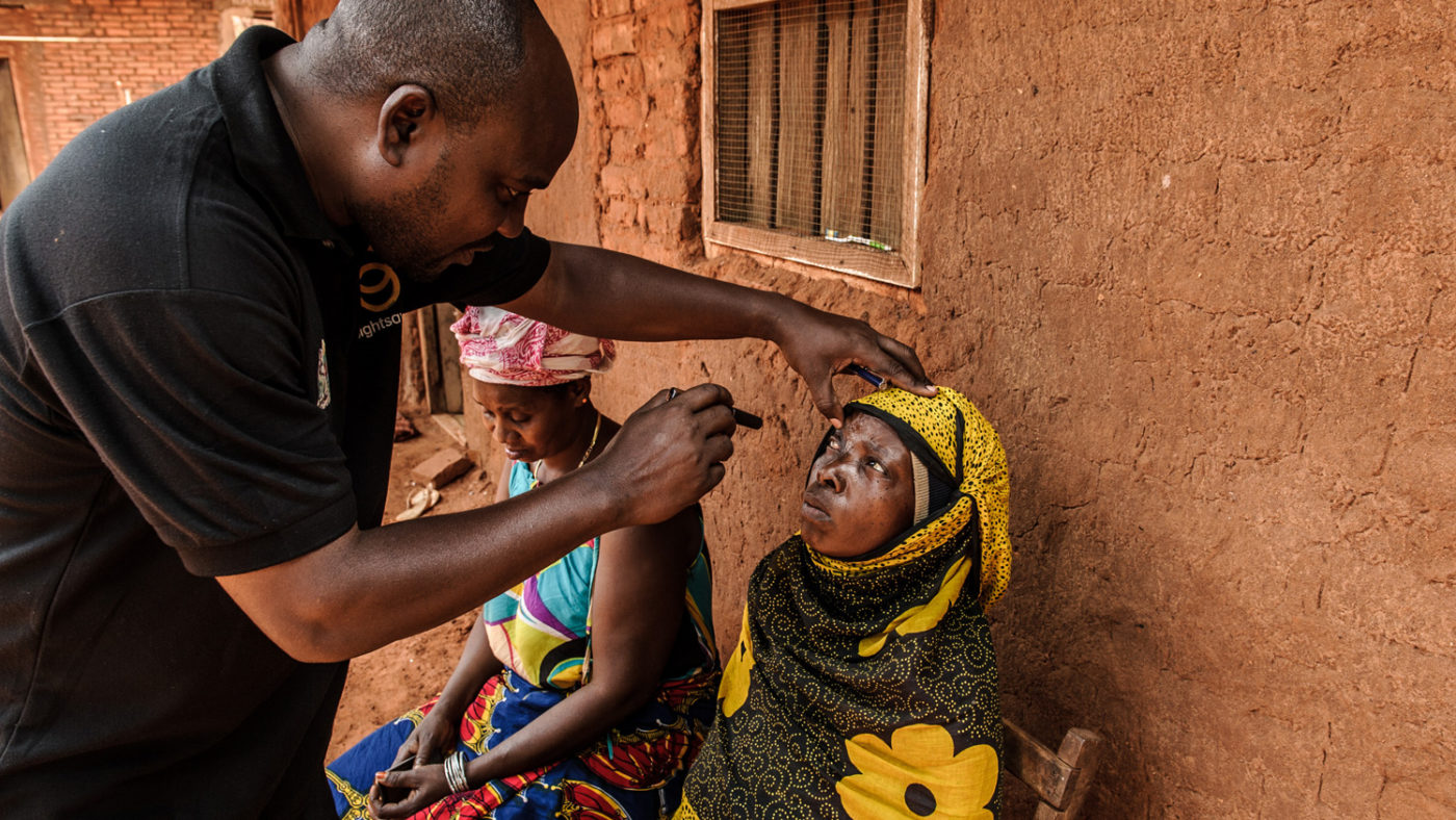 A doctor examining the sore eye of a woman with advanced trachoma.