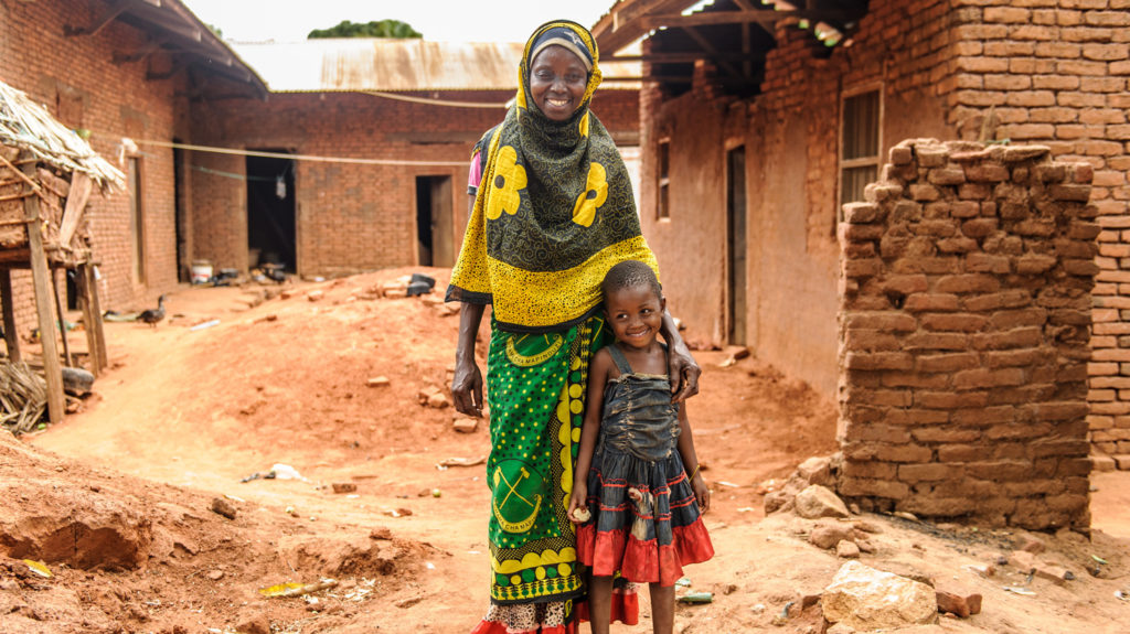 Fatuma and her granddaughter Philly smiling as they stand outside their red clay-brick house