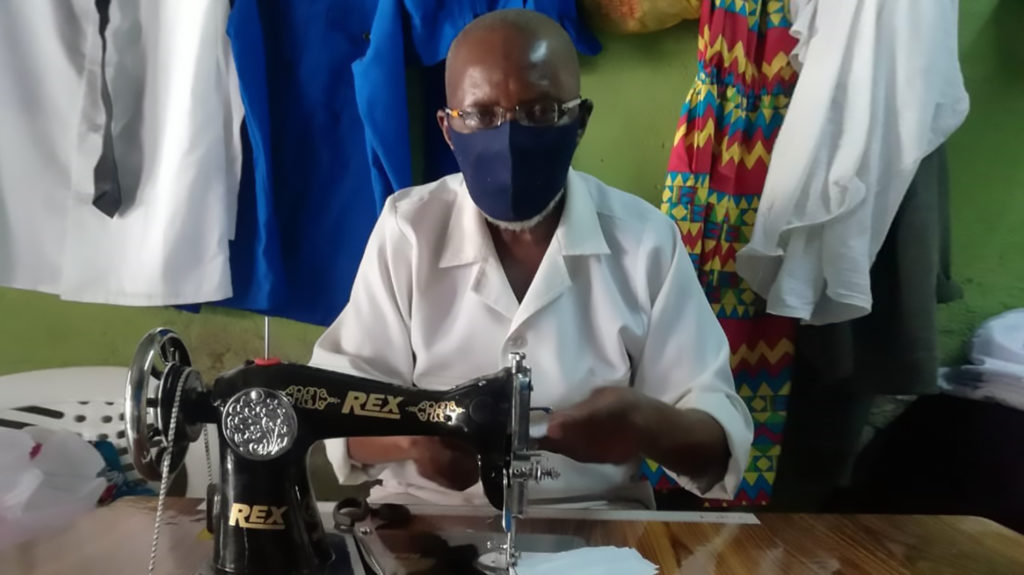 A man working at a sewing machine wearing a face mask.