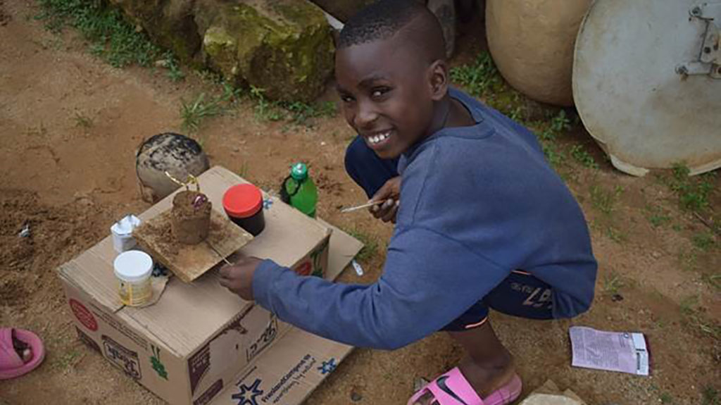 A boy smiles as he plays with his toys outside.