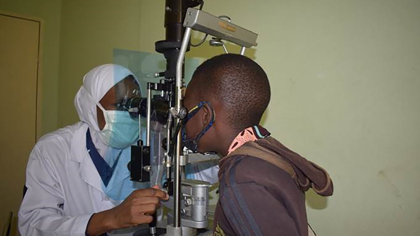 A boy having his eyes checked. The ophthalmologist and the boy are both wearing face coverings and there is a protective screen between them.
