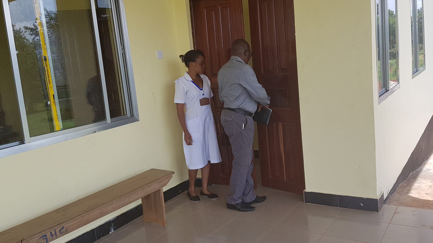 A doctor and a nurse stand outside the clinic.