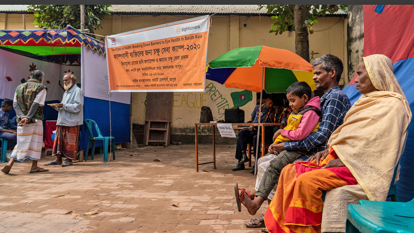 A woman, man and child sit next to a banner, promoting Sightsavers free eye health screening for the Bihari community.