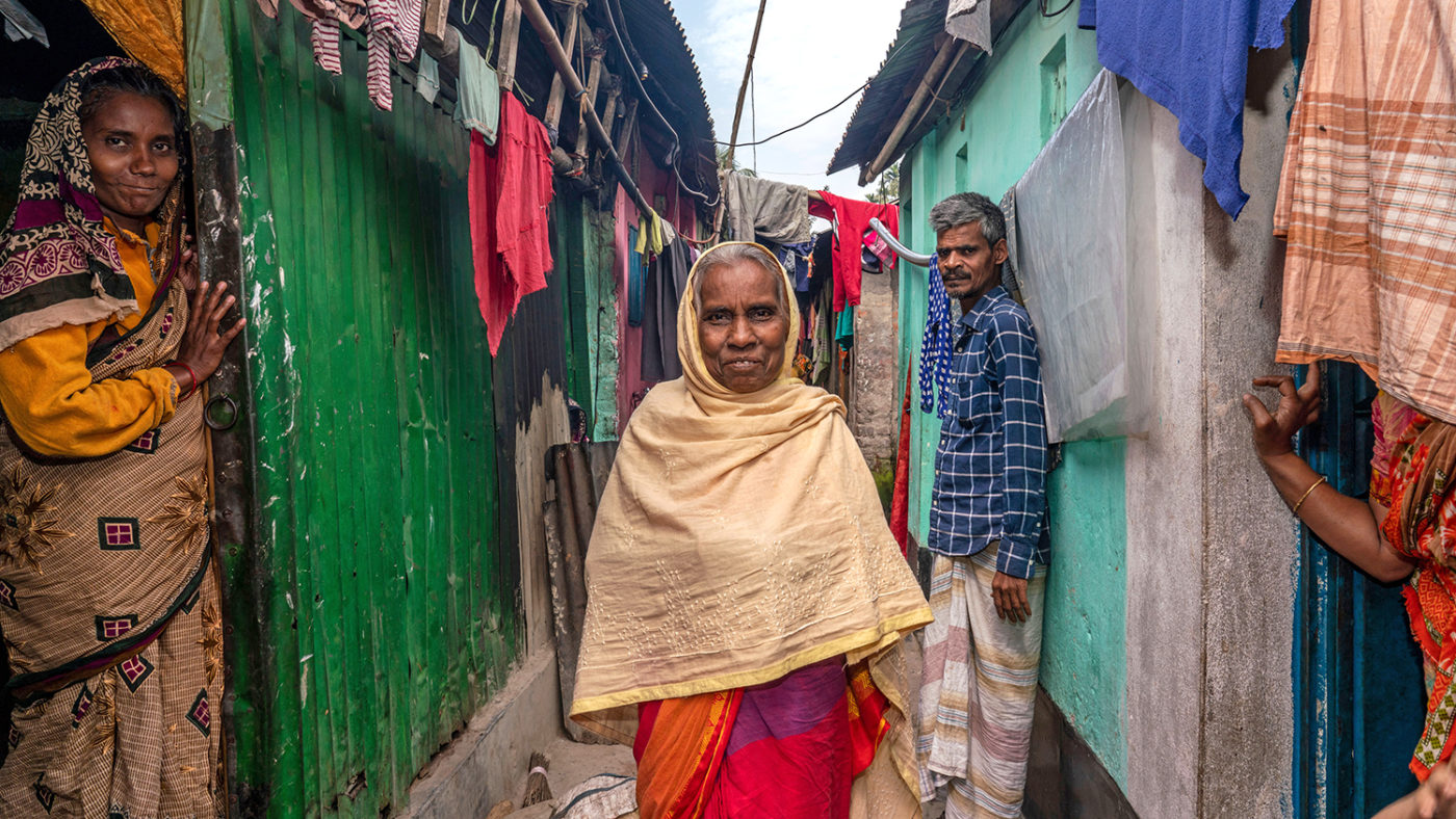 Two Two women and a man stand outside a small home in an informal urban settlement.
