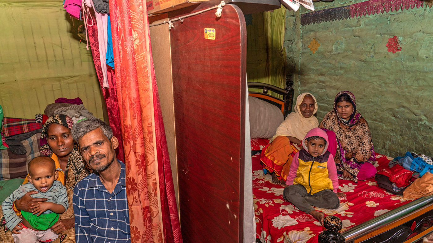 A family sit on beds inside a small room.