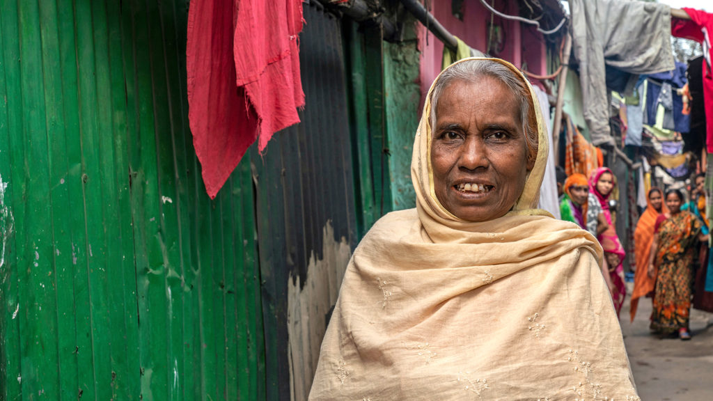 An older women outside her home.