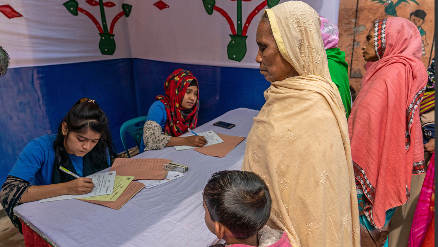 A woman with a child at a registration desk.