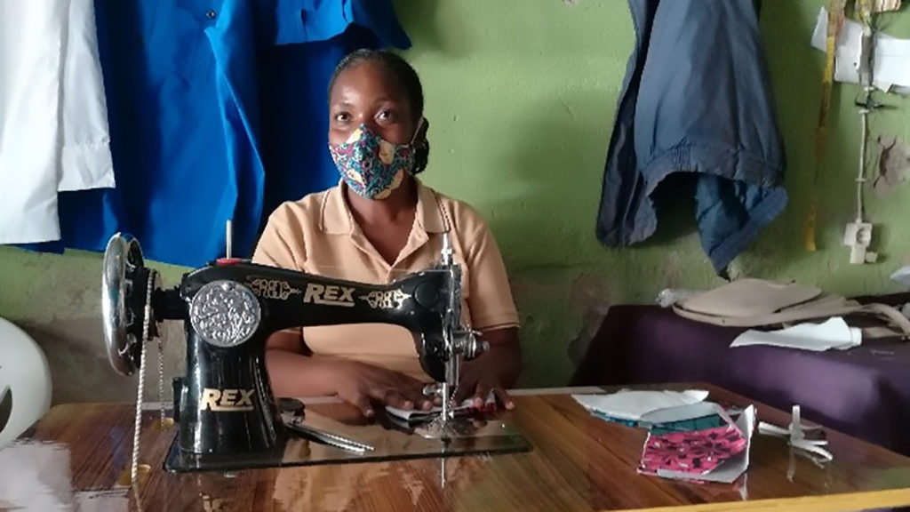 A woman working at a sewing machine wearing a face mask.