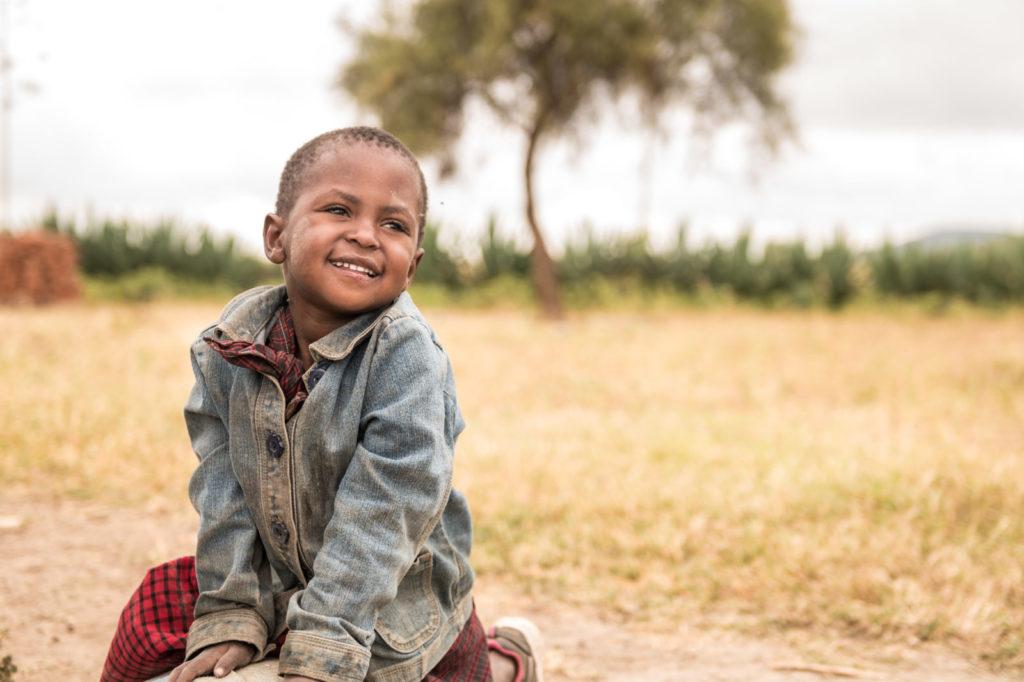A little boy smiling outside.