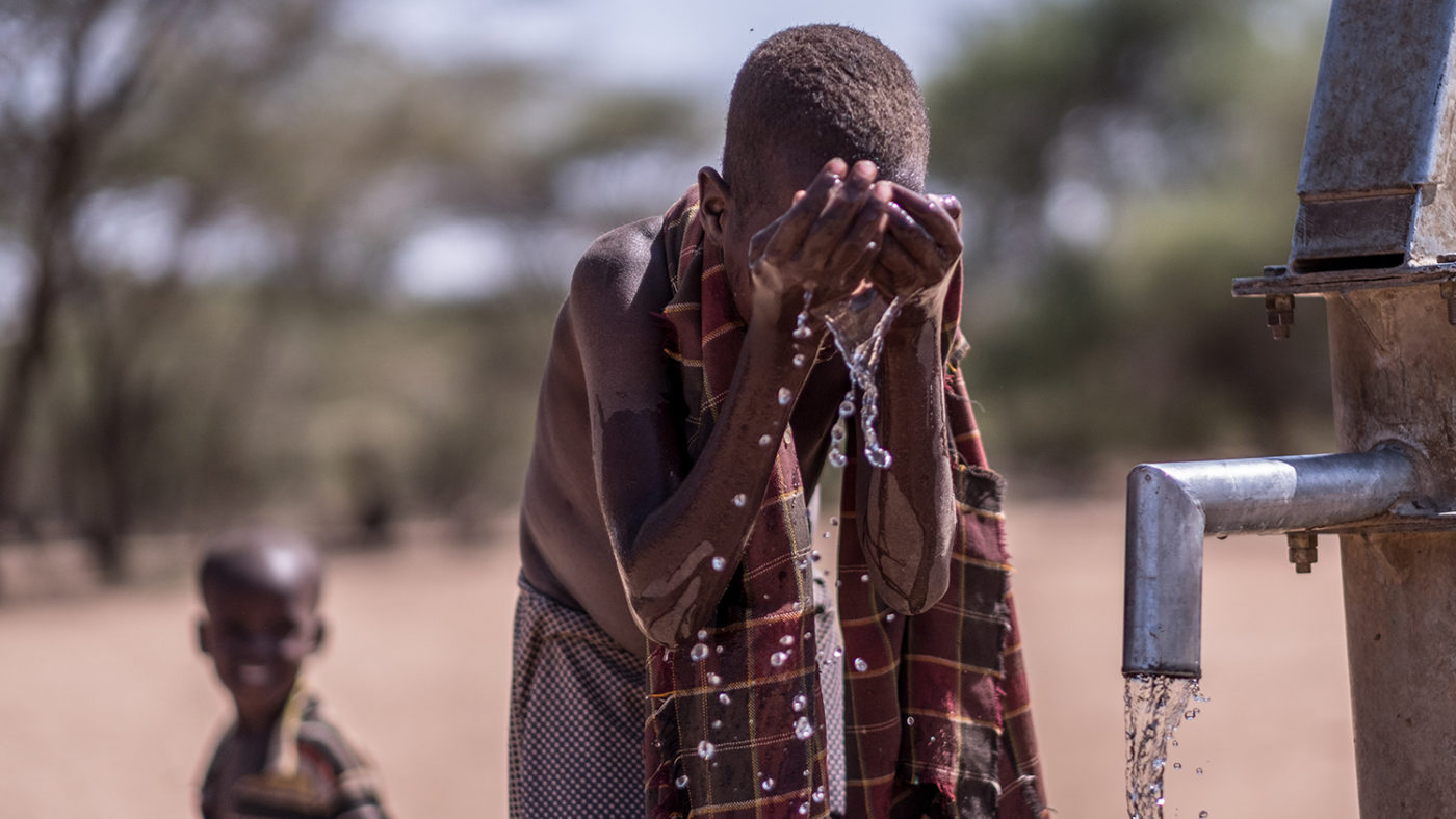 A boy washes his face at a well.