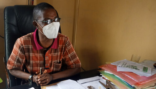 A man sits in an office wearing a face covering
