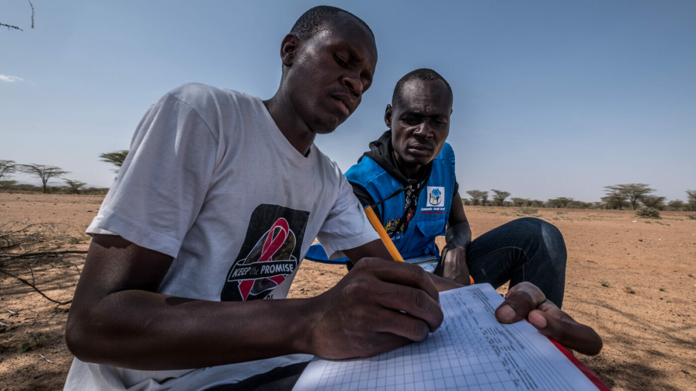 Two volunteers sit on the ground. One is writing on a piece of paper.