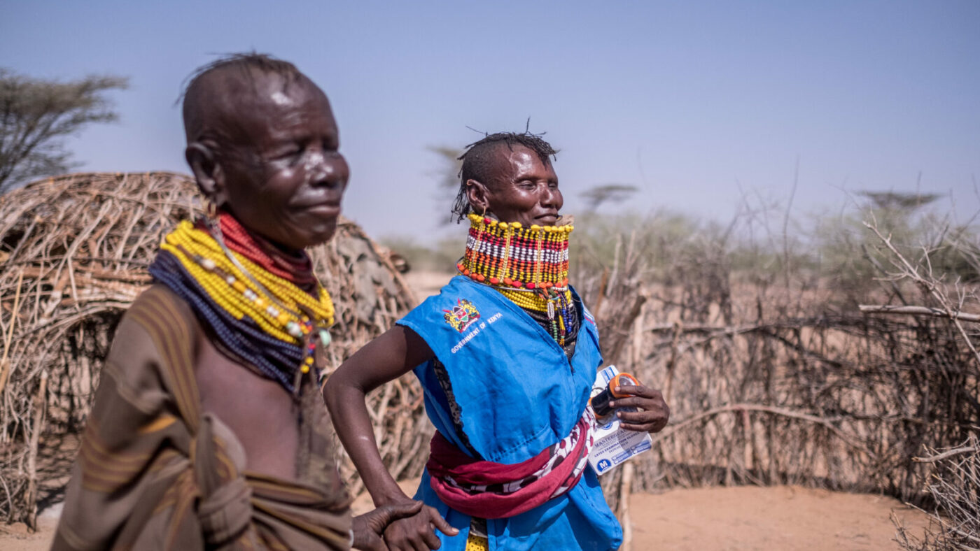 Two people in traditional clothing stand outside in remote Turkana, Kenya.