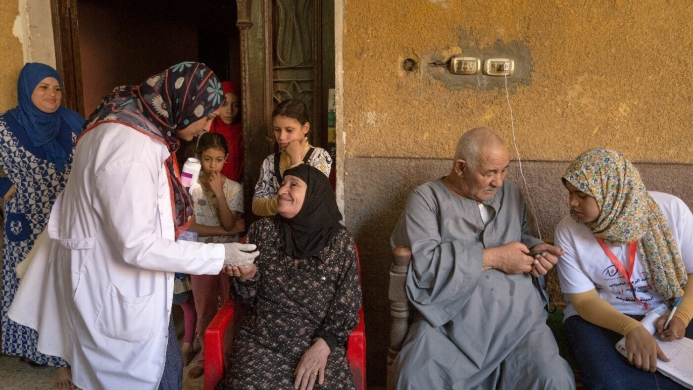 A community volunteer distributes medication to protect a family in Matay, Egypt.