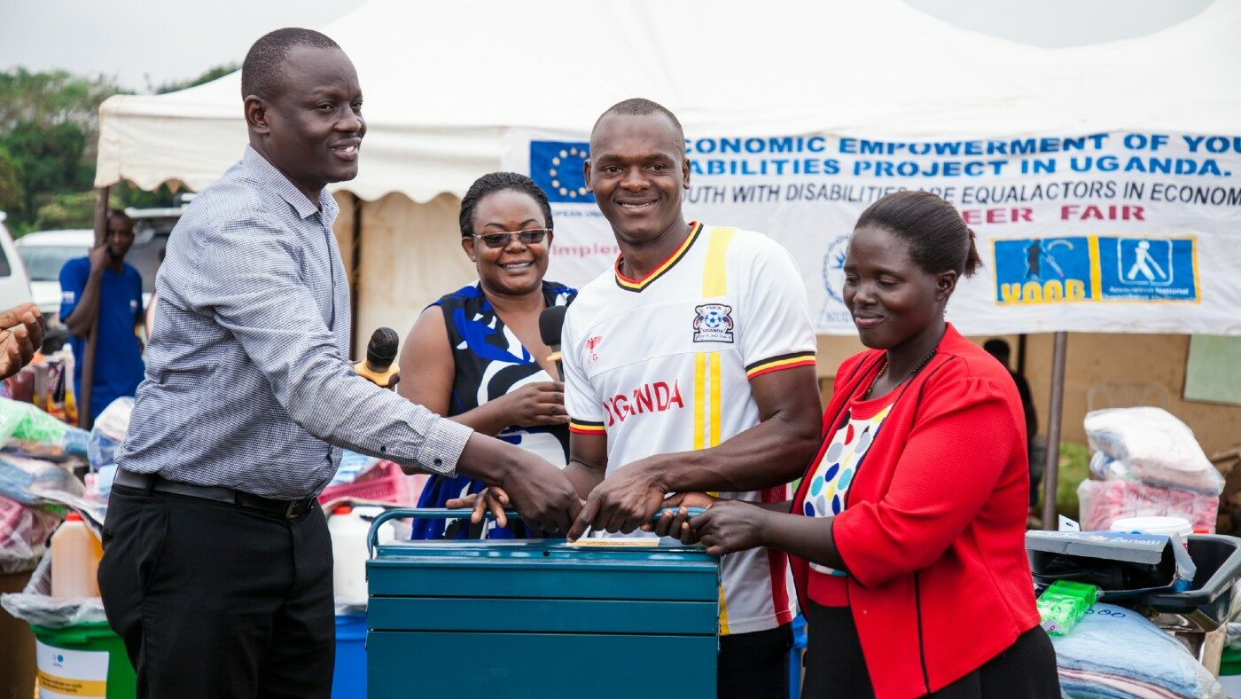 A Masindi district official and the Sightsavers programme manager hand over a motor repair tool kit to Sharif at the careers fair.