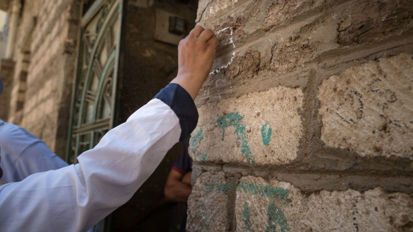 A community volunteer marks the outside of a house with chalk in Matay, Egypt.