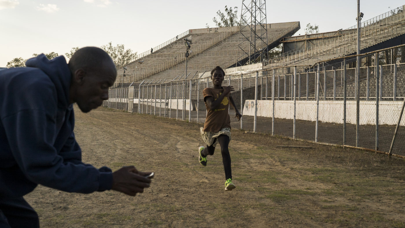A young woman runs on a training track while a man times her with a stopwatch.