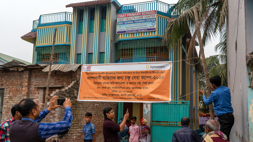 Men putting up a sign to welcome people in Rangpur, Bangladesh to a free eye screening camp.