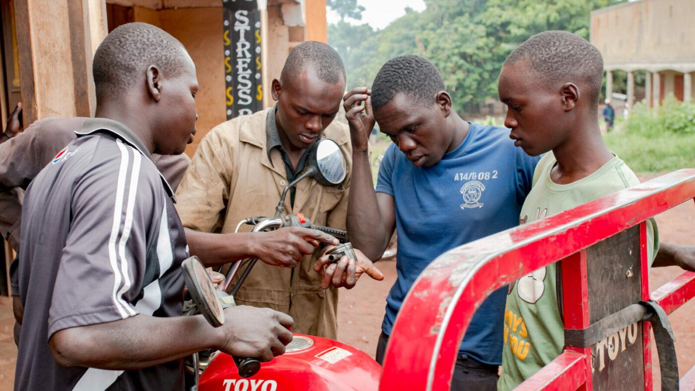 Four men stand around a car.