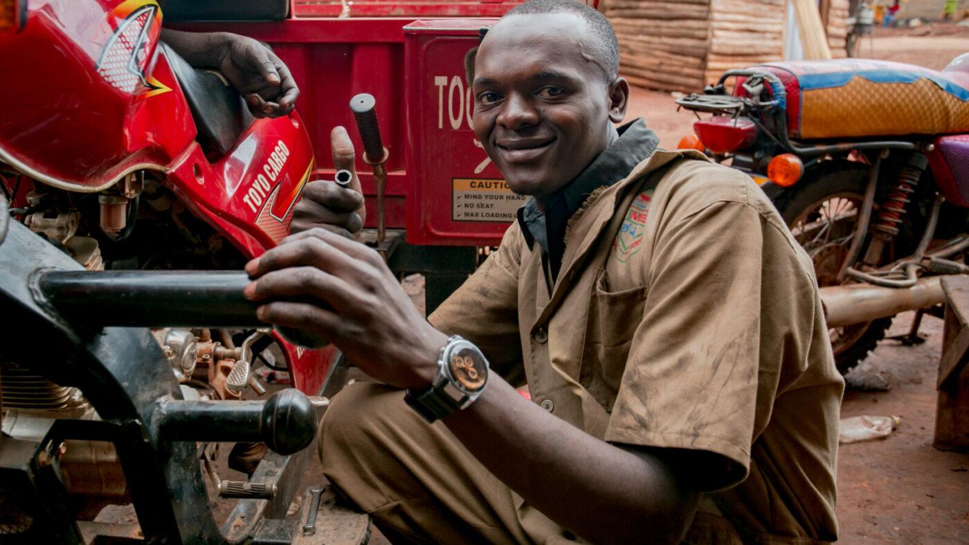 A man fixes a vehicle.