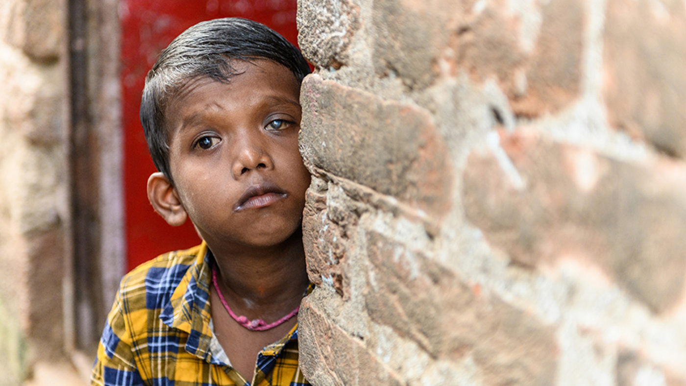 Sanjit standing partially hidden behind a wall whilst looking towards the camera. The cataracts are noticeable in his eyes.