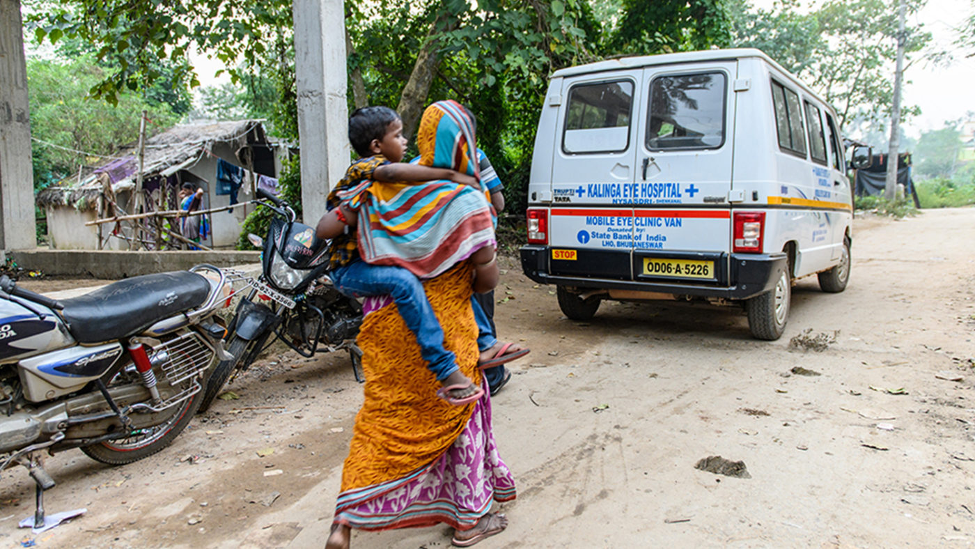Sanjit being carried by his mother, Pramila, towards the vehicle that will be taking his to hospital for his cataract surgery.