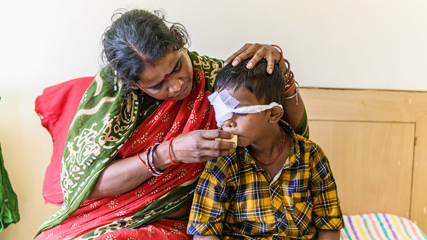 Sanjit drinking from a cup, with help from his mother. His right eye is covered by a bandage as his cataract has been operated on.