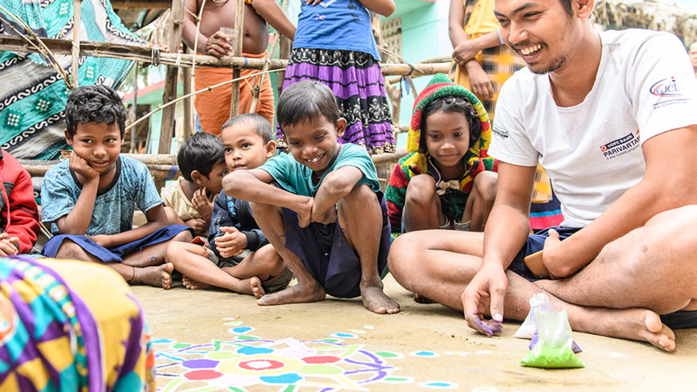 Sanjit sitting happily amongst other children, participating in a game.