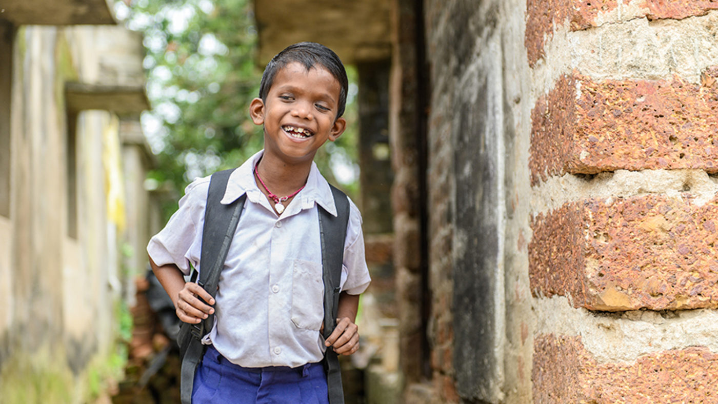 Sanjit happily looking towards the camera as he independently walks towards school.