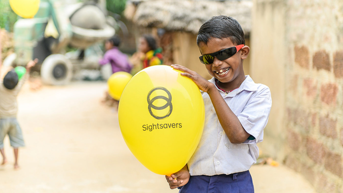 Sanjit holding up a Sightsavers-branded balloon. He is wearing sunglasses.