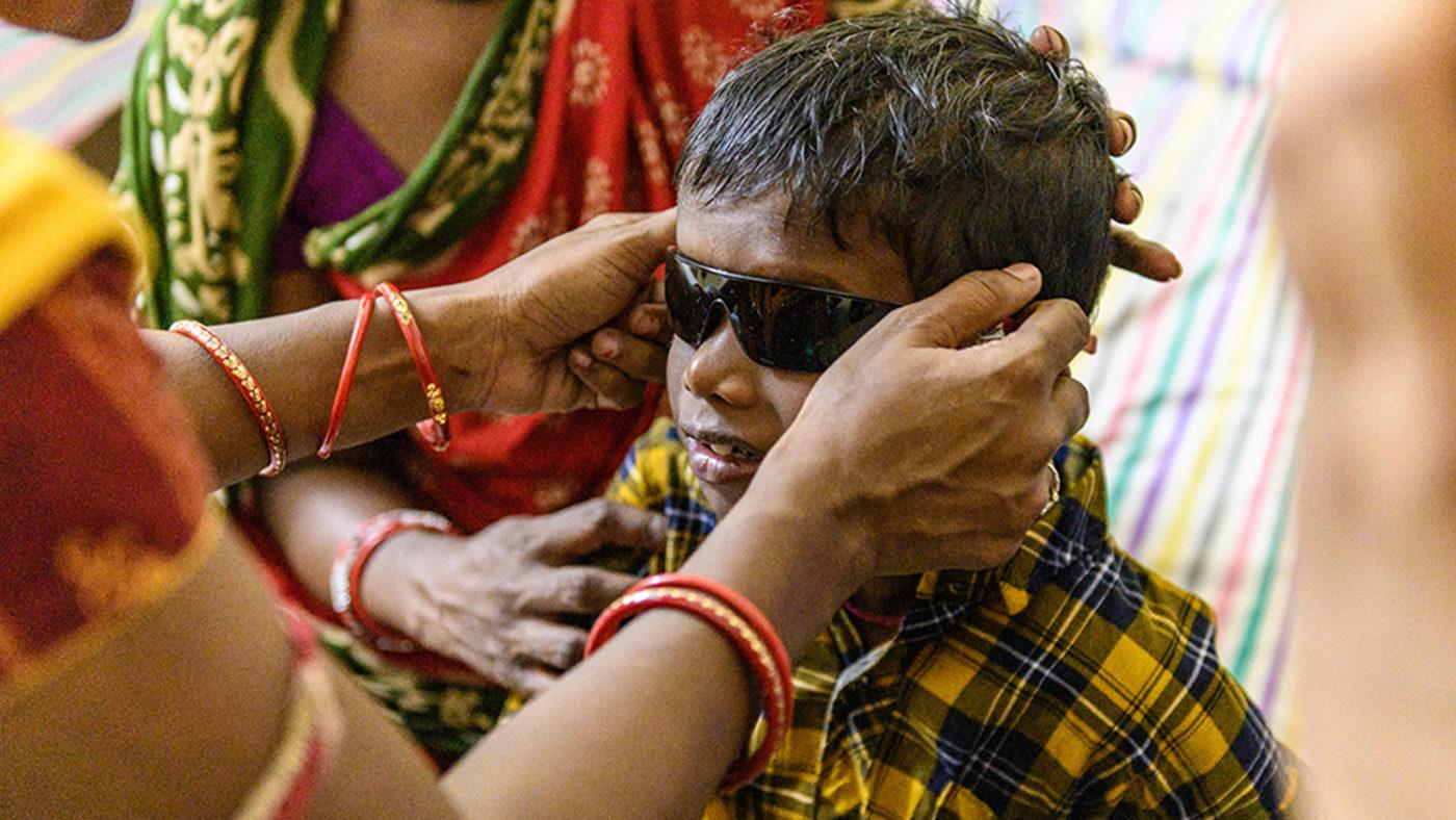 A nurse helps Sanjit put on some sunglasses.