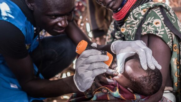 A volunteer inspects a baby's eyes for signs of trachoma.