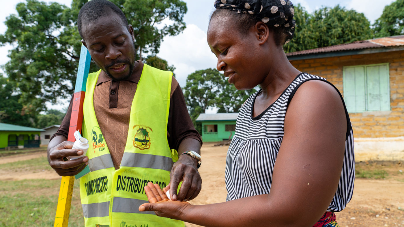 A community volunteer distributed treatment to protect against neglected tropical diseases to a woman.