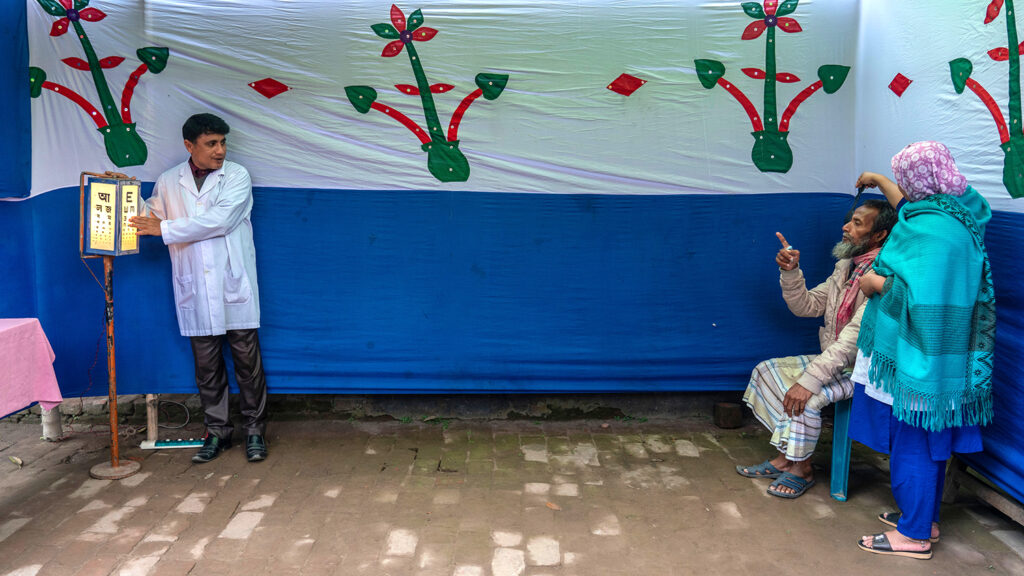 A doctor conducts an eye sight test.