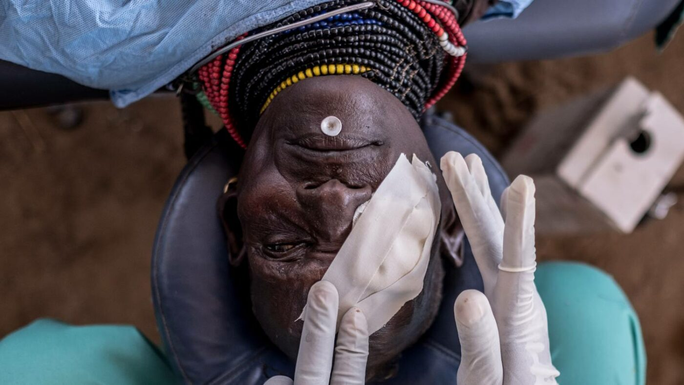 Bandages are applied to a patient wearing traditional clothing on an operating table after a successful trachoma operation