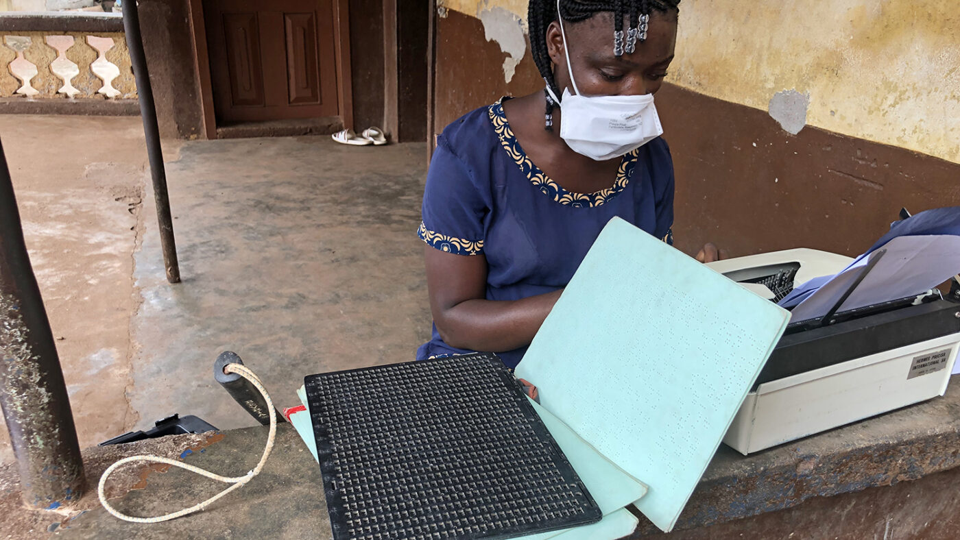A girl with a face mask on, next to braille writing material.
