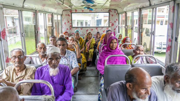 Inside of a bus with many older people sitting.
