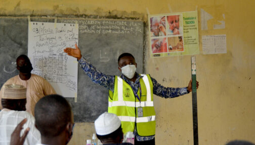A man wearing a mask gives a demonstration to distributors in a school classroom.