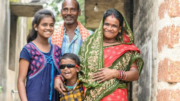A young boy, Sanjit, standing and smiling with his father, mother and older sister.