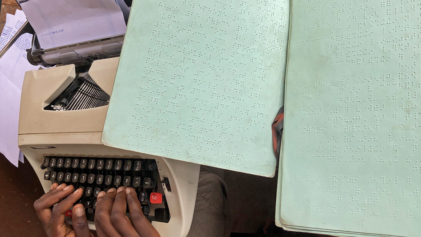 Hands on a braille typewriter and sheets of braille notes.