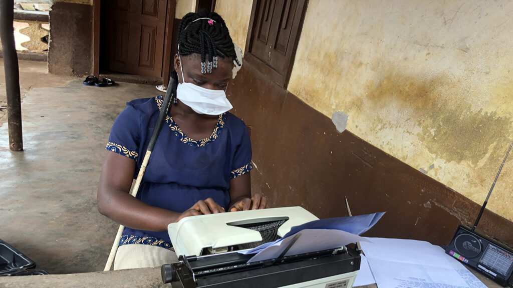 A girl uses a typewriter while wearing a face mask.
