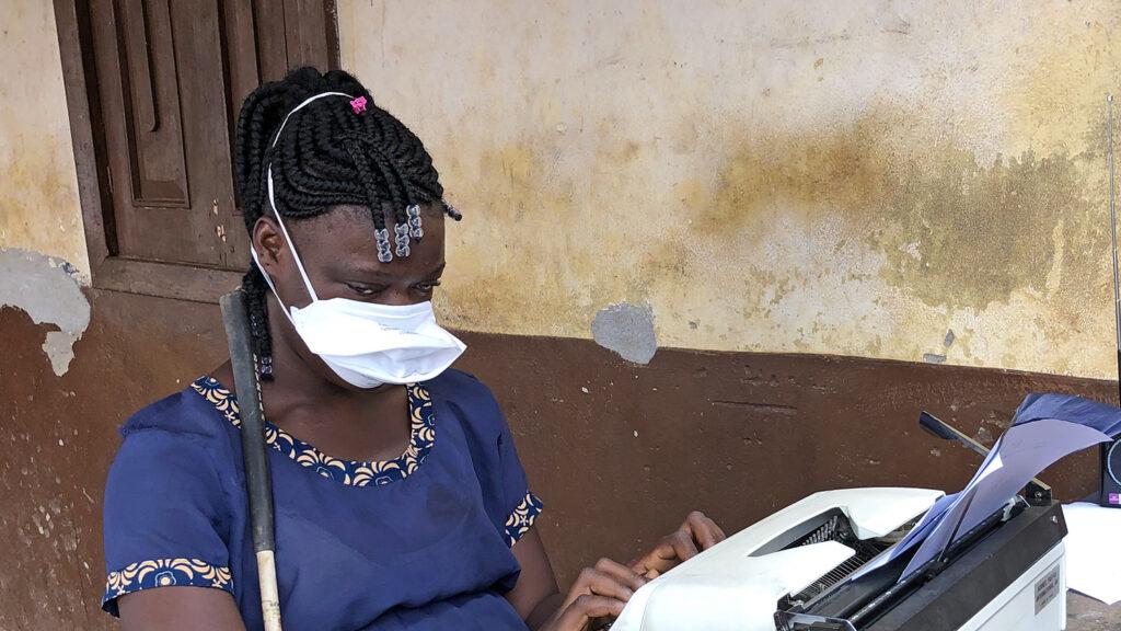 A girl typing on a typewriter.