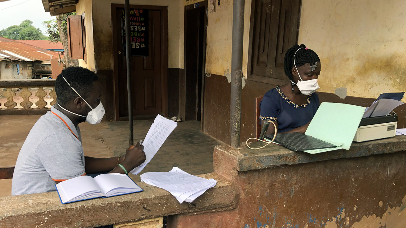 A man and girl sit outside with face masks on.