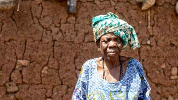 An elderly lady in colourful traditional clothing stands in front of a wall.