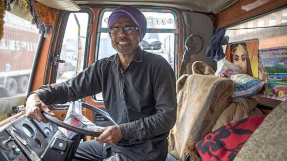 A man with glasses, smiling while sat in his truck.